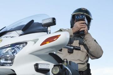 Patrol officer sits on motorcycle looking through pseedometer