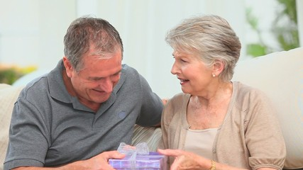 Retired man offering a gift to his wife