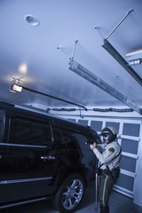 Nightwatch patrolman checks luxury car in garage