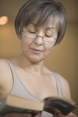 Mature woman with short grey hair, reading