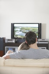 Young couple sit watching television
