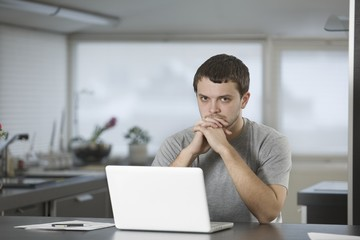 Young man sits leaning on elbows at laptop in kitchen