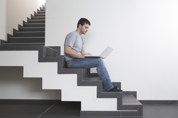 Young man sits on staircase with laptop