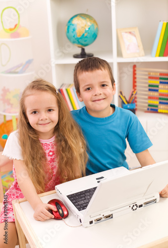 Siblings with laptop computer in their room