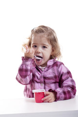 little girl eating youghurt.