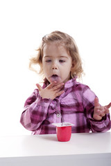 little girl licking her hands full of yogurt
