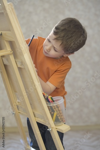 A young boy drawing onto a canvas, with a pot of coloured pencils stood on the ledge of the canvas
