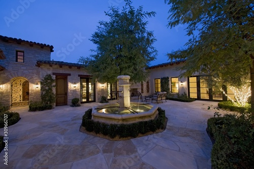 House exterior at night with a fountain, patio furniture and trees, one in which is lit with fairy lights