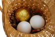 One golden and two white eggs in basket