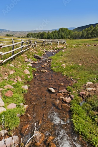 A tranquil, green country scene with a small running stream