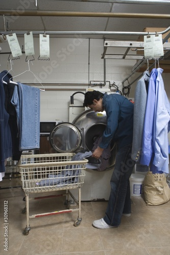 Man loading clothes into the washing machine