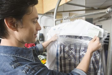 Man working in the laundrette checking clothes