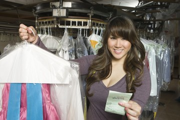 Woman working in the laundrette holding a receipt and clothes