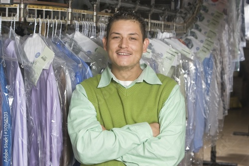 Man working in the laundrette, standing infront of clothes rail