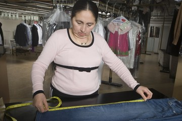 Mature woman measuring in the laundrette