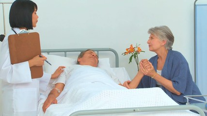 Woman and her sick husband talking with the nurse