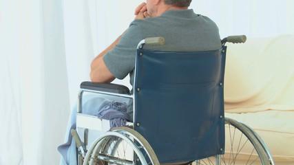 Man in a wheelchair looking through the window