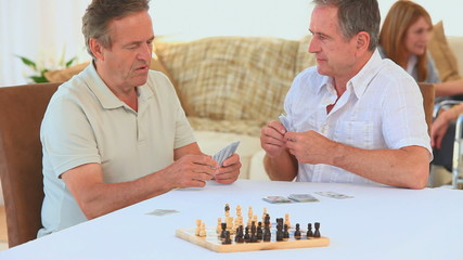 Elderly friends playing cards