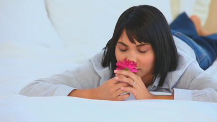 Cute asian woman smelling a flower