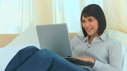 Good looking asian woman working on a laptop