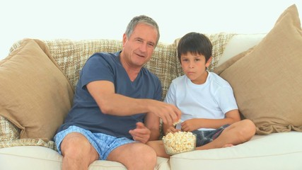 Grandfather and his grandson watching a match