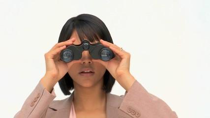 Asian woman in suit using binoculars