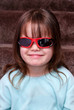 Young girl looking cool with sunglasses on indoors