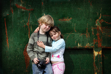 Young brother and sister pose for a photograph with their camera