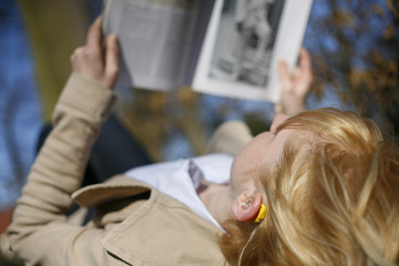 Junge Frau mit Hörgerät liest Zeitung im Wald
