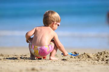 Niño jugando en la playa con la arena