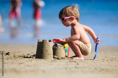 Niño jugando en la arena de la playa - 30993909
