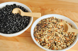 Bowls of uncooked wild rice and black beans