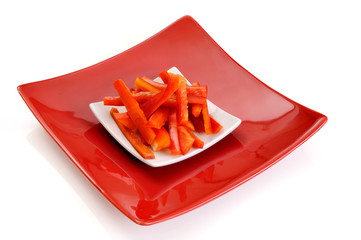 Red pepper strips on a red dish