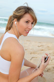 Portrait of woman exercising on the beach with headphones on