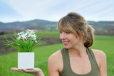 Portrait of woman holding flower pot in green field