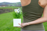Closeup of woman holding flowerpot in green field