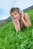 Beautiful woman in green field with headphones on