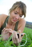 Beautiful woman listening to music in natural field