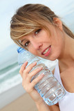 Closeup of beautiful woman drinking water from bottle