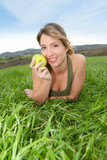 Beautiful woman eating a green apple in nature