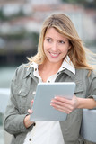 Beautiful blond woman using electronic tablet in town