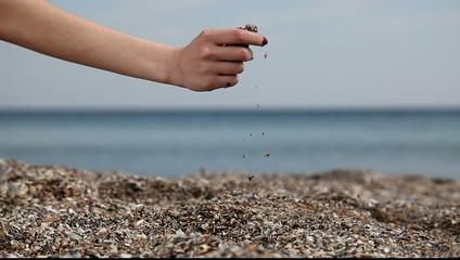 Female hand keep sand at the beach.