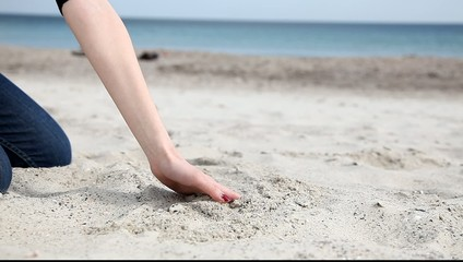 Female move hand over sand