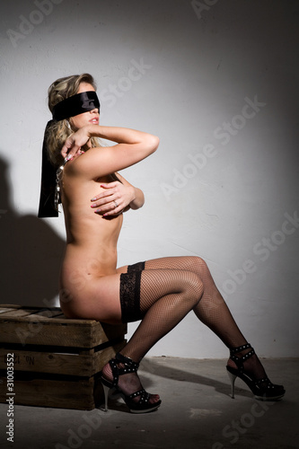 beautiful sexy nude girl with blindfold and bound in dungeon