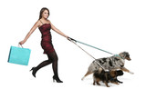 Young woman walking dogs on leash and holding shopping bag poster