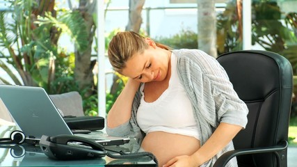 Very tired pregnant woman at an office