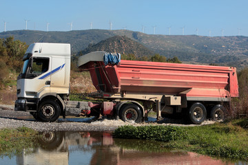 Heavy lorry or truck drives through small river