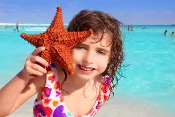 little tourist girl holding starfish tropical beach