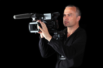 Young male videographer shooting at night or in studio