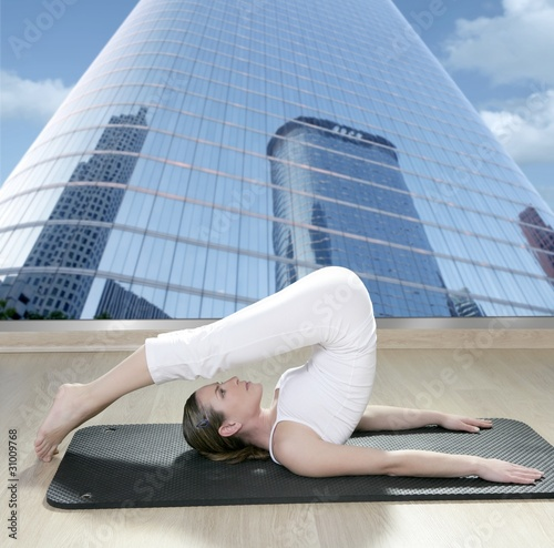 black mat yoga woman window view city urban buildings